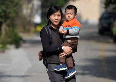 A mother carries her son on a street in Shanghai on 16 November 2013. Days after a key meeting in Beijing the Communist leadership announced that it would allow couples to have two children if one parent is an only child, widening the exemptions from a rule imposed in the late 1970s to control China's population. (Photo: AAP).