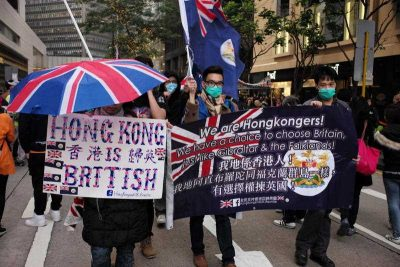 Protesters held signs and carried flags and umbrellas with the British Union Jack while they marched through the streets of Hong Kong in support of Occupy Central on 1 February 2015. (Photo: AAP).