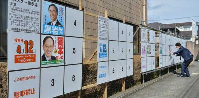 A campaign staff puts up posters for candidates in local assembly elections in Sagamihara, Kanagawa Prefecture on 3 April 2015.  (Photo: AAP)
