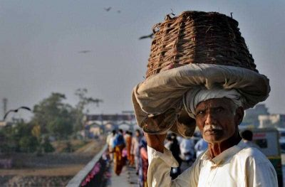 A Pakistani labourer carries an empty fruit basket following his day's work in Lahore on November 12, 2011.  (Photo: AAP).