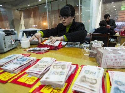 A Chinese clerk counts RMB (renminbi) yuan banknotes at a branch of China Construction Bank, 15 February 2015. In 2014, China became a net capital exporter for the first time. (Photo: AAP)