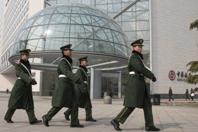 Paramilitary police patrol near the headquarters of the Bank of China in Beijing, 7 March 2015. The Xi administration has implemented a flagship policy to thoroughly clean up corruption in China. (Photo: AAP).