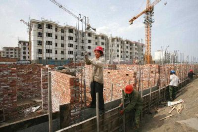 Chinese workers construct residential buildings of a government-funded housing project in Tiemenguan city, China, 2 May 2015. (Photo: AAP).