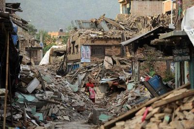 A Nepalese woman walks past damaged houses following an earthquake in Kathmandu on 26 May 2015. (Photo: AAP)