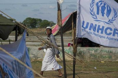 A Rohingya migrant walks past the UNHCR flag at a confinement area in Kuala Cangkoi in Aceh. More than 3,500 migrants including Bangladeshi and Rohingya from Myanmar have swum to shore or been rescued off the coasts of Malaysia, Indonesia, Thailand and Bangladesh since the migrant crisis erupted early May 2015. (Photo: AAP)