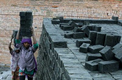 Indian labourers work at a brick manufacturing unit on the outskirts of Hyderabad on 2 March 2015. India's factory output in February grew at its slowest pace in five months as business demands remained dim. (Photo: AAP)
