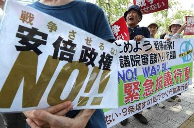 People shout slogans as they hold a banner during a rally to protest against controversial security bills which would expand the remit of the country's armed forces, in front of the National Diet in Tokyo on 27 July 2015. (Photo: AAP)