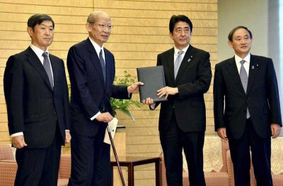 Japanese Prime Minister Shinzo Abe accompanied by Chief Cabinet Secretary Yoshihide Suga poses as he receives a 38-page report from the government panel commissioned by Abe to review the country's recent history in Tokyo, 6 August 2015. (Photo: AAP).