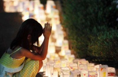 A girl offers a prayer for A-bomb victims before lanterns placed at the Peace Memorial Park in Nagasaki, Japan's southern island of Kyushu on 8 August 2015. (Photo: AAP)