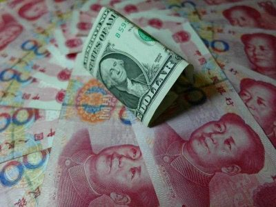 Yuan banknotes and US dollars are seen on a table in Yichang, central China's Hubei province on August 14, 2015. (Photo: AAP)