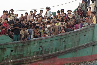Migrants sit on their boat as they wait to be rescued by Acehnese fishermen on the sea off East Aceh, Indonesia, Wednesday, May 20, 2015. (Photo: AAP)