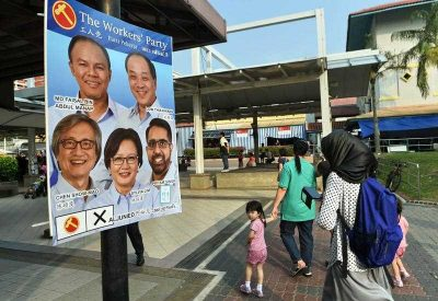 Residents walk past an election candidates poster of the opposition Worker's Party (WP) in Aljunied GRC at Hougang in Singapore on 5 September 2015, ahead of Singapore's 11 September election. (Photo: AAP)