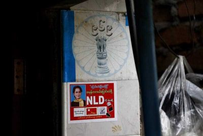 The logo of Buddhist extremist group Ma Ba Tha and the National League for Democracy party campaign sticker lie on a wall in Yangon, Myanmar, 8 September 2015. (Photo: AAP).