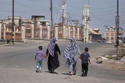 Kashmiri Muslim women walk with children on a deserted street during a curfew in Kashmir, 12 September 2015. The most recent data released on religion in India was from 2011. (Photo: AAP)