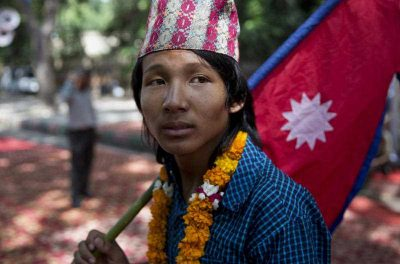 A boy carries the national flag of Nepal during a protest in New Delhi, India, Tuesday, Sept. 22, 2015 (Photo: AAP)