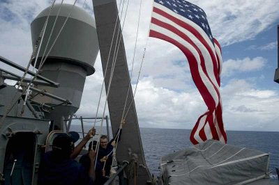 US Navy personnel raise their national flag during a training exercise aboard the USS John S. McCain in the South China Sea near waters claimed by Beijing. (Photo: AAP).