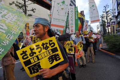 A demonstrator holds a sign against the new legislation that would allow the military to deploy overseas, in Tokyo outside of Japan's parliament against new legislation on September 23, 2015 (Photo: AAP)