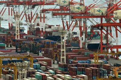 """Gantry cranes and shipping containers are seen beside a vessel at the cargo terminal area of Tokyo port on October 6, 2015. Japanese Prime Minister Shinzo Abe hailed a deal to create the world's largest free trade area 6 October as the start of a """"new century"""" for Asia, and expressed hope China might one day join the historic accord. (Photo: AAP)"""