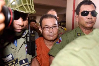 Cambodian senator Hong Sok Hour (C), who belongs to a CNRP-affliated party, is escorted by police at Phnom Penh municipal court on October 7, 2015, in a case in which he could be jailed for 17 years after a court charged him on August 16 over the posting of a disputed document on social media about the border with Vietnam. (Photo: AAP)