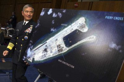 Admiral Harry B. Harris of US Pacific Command walks past a photograph showing an island that China is building on the Fiery Cross Reef in the South China Sea while preparing to testify on Capitol Hill in Washington, 17 September 2015. (Photo: AAP).