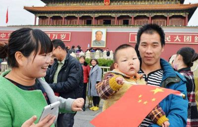 A young couple with a child visit Tiananmen Gate in Beijing on Nov. 17, 2015. (Photo: AAP)