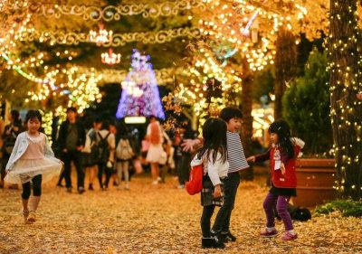 Children scatter autumn leaves into the air at dusk in Tokyo, Japan, 21 November 2015.  (Photo: AAP)