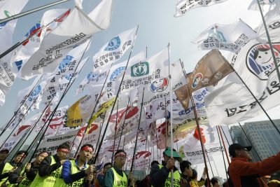 Unionised civil servants hold their union flags during a rally to oppose the government's bid to overhaul the public pension system near the National Assembly in Seoul, South Korea, 28 March 2015. South Korean President Park Geun-hye called for parliamentary endorsement of a bill meant to reform the pension system for civil servants in the latest appeal to reduce the government's growing pension deficit. (Photo: AAP)