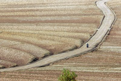 A lone farmer walks on a dirt road beside dry terrace fields in rural Liangshan Yi Autonomous Prefecture, Sichuan province, China (Photo: AAP)