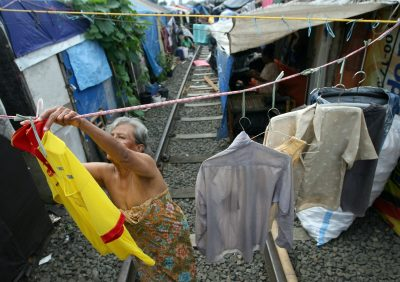 Indonesian woman hangs clothes on the railway near her temporary hut at a slum area in Jakarta, Indonesia (Photo: AAP)