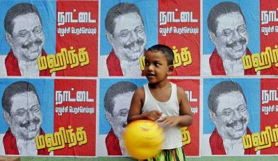 A Sri Lankan boy stands next to a wall pasted with election campaign posters of Sri Lankan President Mahinda Rajapaksa in Colombo, Sri Lanka. (Photo: AAP)