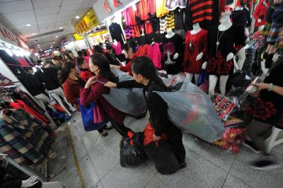 People deliver clothes at the Dacheng Clothes Market in Tudi Village. (Photo: AAP)