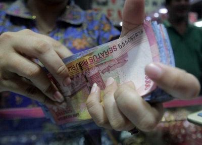 n Indonesian vendor counts Rupiah notes at a market in Jakarta, Indonesia, 10 December 2015. (Photo: AAP)
