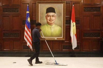 A maintenance worker works near a portrait of Malaysian Prime Minister Najib Razak during the 69th United Malays National Organisation general assembly in Kuala Lumpur, Malaysia, 8 December 2015. (Photo: AAP).