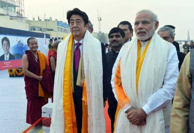 A handout picture made available by the Indian Press Information Bureau (PIB) shows Japanese Prime Minister, Shinzo Abe (C), with the Indian Prime Minister, Narendra Modi (R), receiving a traditional welcome on their arrival to attend the traditional Ganga 'aarti' or worship of the holy Ganges river in Varanasi, India, 12 December 2015. (Photo: AAP)