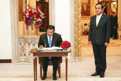 Cambodian Prime Minister Hun Sen signs a guest book as his Thai counterpart stands at Government House in Bangkok, Thailand, 18 December 2015. (Photo: AAP).