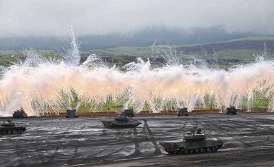 Japan Ground Self-Defense Force's Type-89 armored combat vehicles flare up a smoke screen during an annual live firing exercise at Higashi Fuji range in Gotemba, southwest of Tokyo. (Photo: AAP)