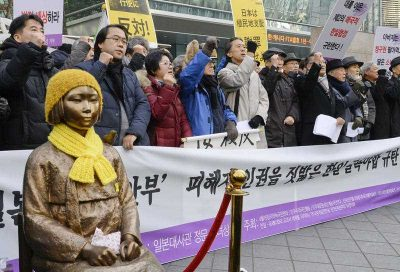 People protest a recent landmark deal between Japan and South Korea over women forced to work in Japan's wartime military brothels, near a bronze statue of a girl symbolizing the 'comfort women' issue located in front of the Japanese Embassy in Seoul on December 30 2015. (Photo: AAP).
