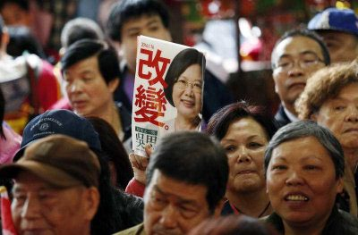 A supporter of Taiwan's Democratic Progressive Party presidential candidate Tsai Ing-wen holds her portrait and a slogan that reads 'Change' as Tsai visits a temple in Taipei, Taiwan, 6 January 2016. (Photo: AAP).