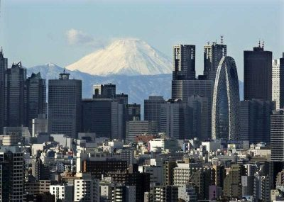 Snow-covered peak of Mount Fuji is seen through Shinjuku skyscrapers in Tokyo, Japan, 20 January 2016. (Photo: AAP).
