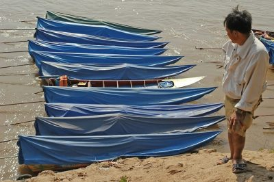 A Laotian looks at speed boats in Kho Liaw, the Mekong River harbour in Vientiane, Laos. (Photo: AAP)