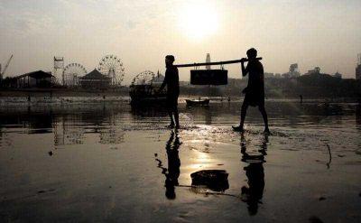 Fishermen carry the caches near the shore of the Arabian Sea in Mumbai, India. (Photo: AAP)