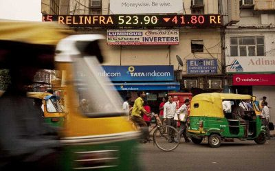 A stock ticker displays closing figures for the Sensex Index on a street in New Delhi, India. (Photo: AAP).