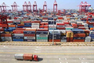 A container truck passes by piles of containers at a terminal of Yangshan Deep-water Port in Shanghai, China. (Photo: AAP)