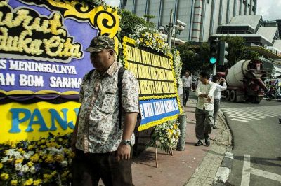 A man looks at floral tributes at the scene of a bomb blast at a police post in Jakarta, Indonesia, on 15 January 2016. (Photo: AAP).