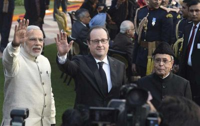 French President Francois Hollande, flanked by Indian Prime Minister Narendra Modi and Indian President Pranab Mukherjee, waves to the media at a reception in New Delhi, India. (Photo: AAP)