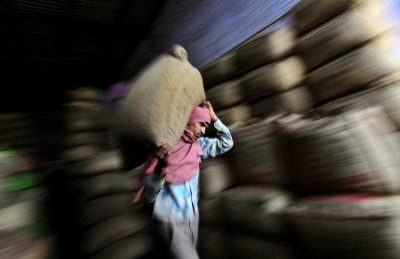 A worker carries a sack of tea in a warehouse in Amritsar, India. (Photo: AP)