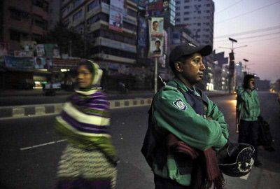 A Bangladeshi woman walks past an armed policeman as he stands guard on a street early in the morning in Dhaka, Bangladesh. (Photo: AAP).