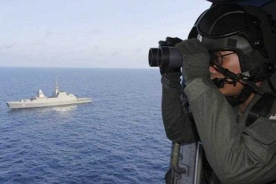 A Singaporean Navy air crew and warship. (Photo: AAP)
