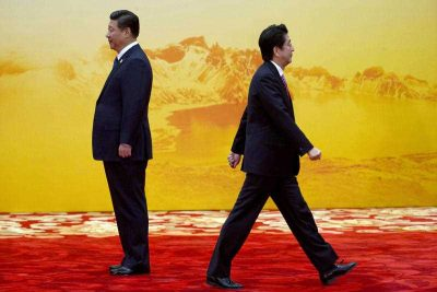 Japan's Prime Minister Shinzo Abe walks past Chinese President Xi Jinping during the 2014 APEC Summit in Beijing. (Photo: AAP)