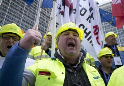 Steelworkers demonstrate China's potential MES status in front of the European Commission building in Brussels during a on 15 February 2016.